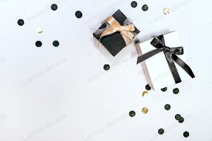 Black and white gift or present boxes and confetti on white background
