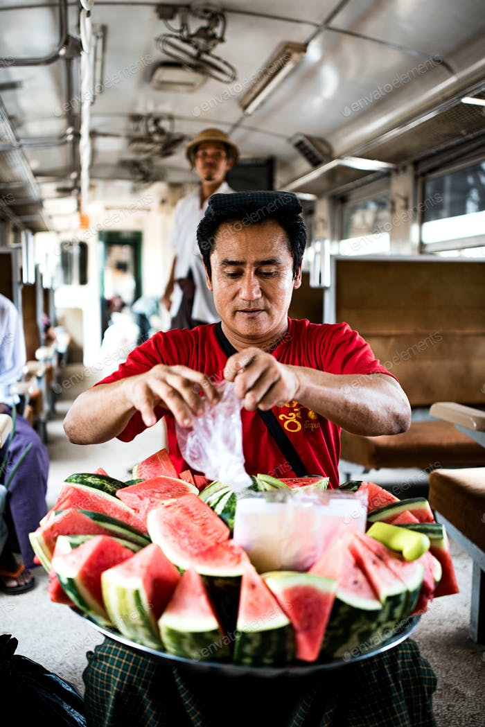 Burmese man selling melon in the train