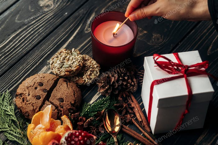 Hand-Beleuchtung Kerze und Geschenk Lebkuchen Kekse Granat Orangen und Gewürze