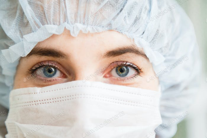 Close-up portrait of young female surgeon doctor or intern wearing protective mask and hat