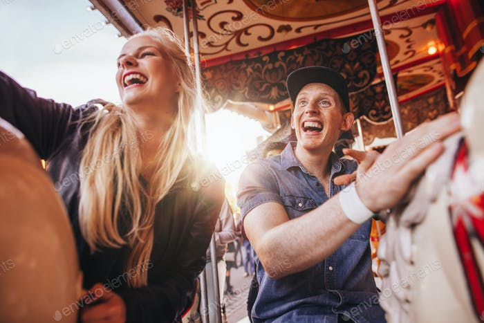 Smiling couple on carousel at fairground