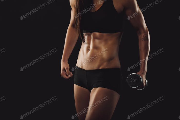 Starke und muskulöse Build Frau mit Hantel trainieren