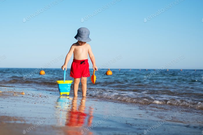 Boy kid in red shorts on the summer beach