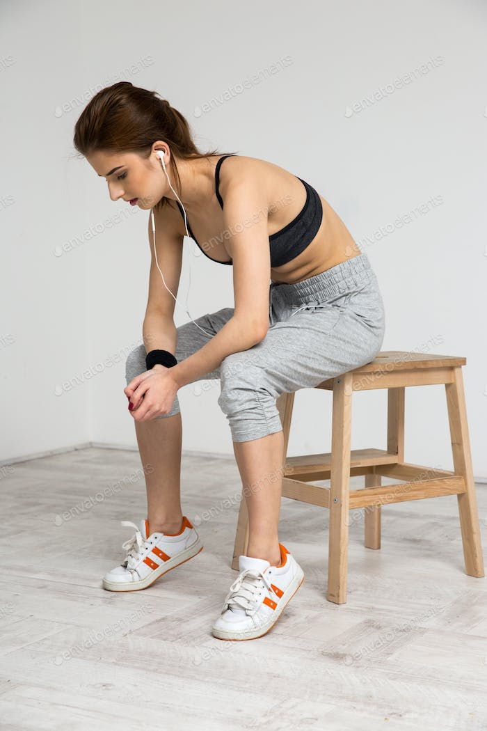 Portrait of a beautiful sports woman sitting on the wooden chair at gym