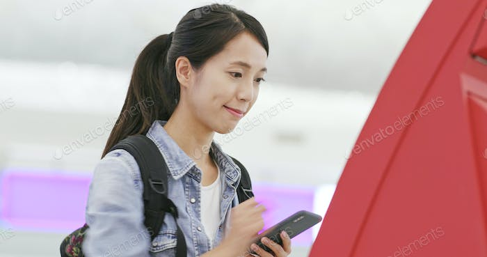 Woman using selfie check in counter in the airport