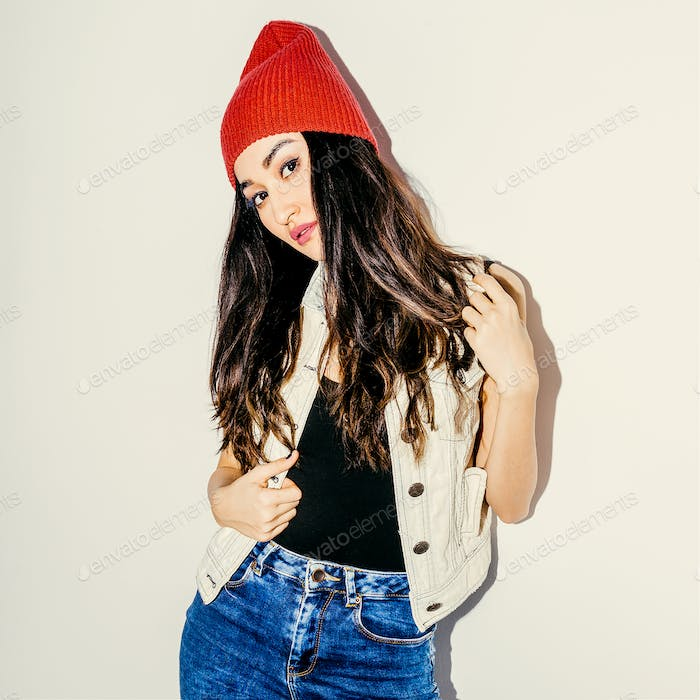Brunette Model in fashion beanie cap and jeans. Urban casual sty