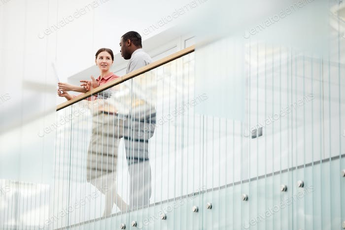 Two Business People Standing on Balcony
