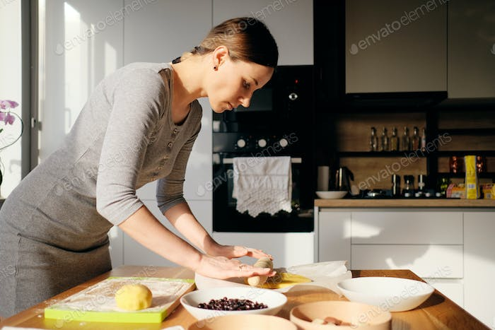 Woman rolls out the dough with a rolling pin in the sun rays