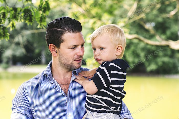 Father carrying son at park
