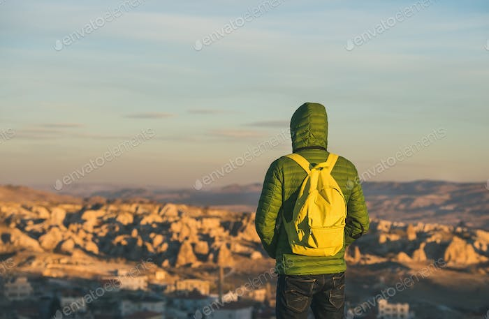 Young man in bright clothing watching sunrise, Cappadocia, Central Turkey