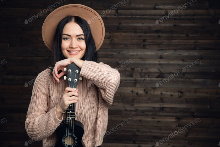 Portrait of a smiling casual woman posing with guitar against wooden plank
