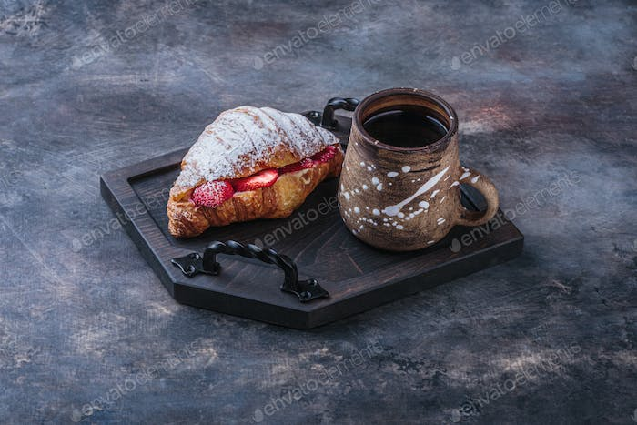 Delicious croissant with strawberry and coffee for breakfast, copy space