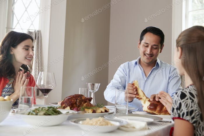 Jewish man sharing challah bread with family at Shabbat meal