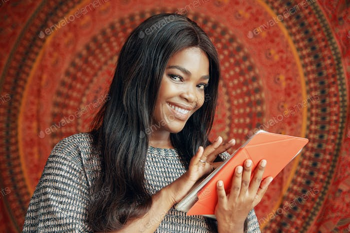 Smiling ethnic woman with tablet