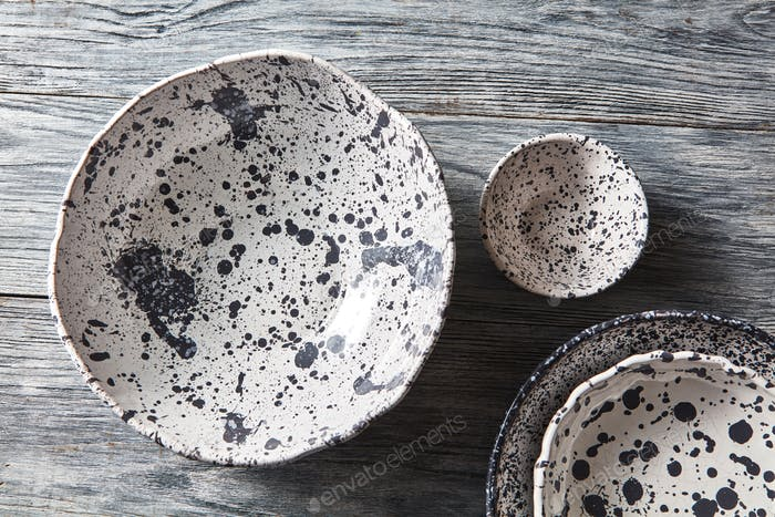 Decorative pottery - bowls, plates covered with glazed on a gray wooden background. Top view of