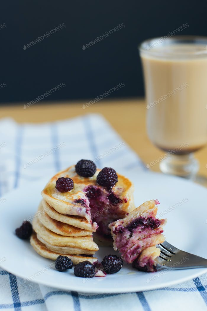 eating of slapjack or oladyi with black raspberry with fork on white plate and cocoa