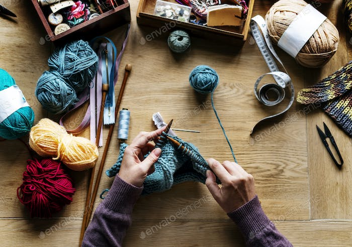 Aerial view of hands knitting on wooden table