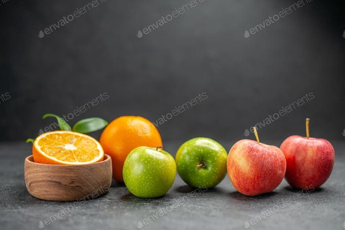 Close up view of benefit fruit salad with fresh oranges and green apple on dark background