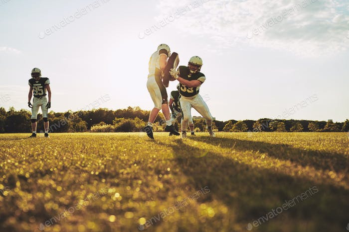 American football teammates practicing tackling on a sports field