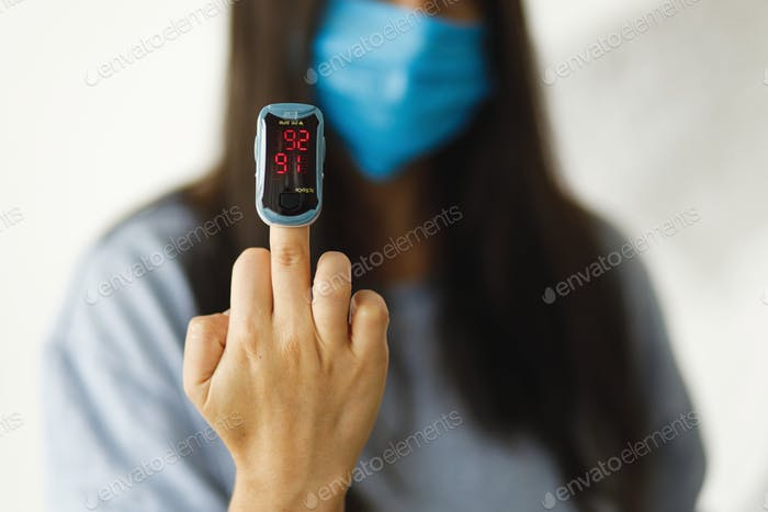 Pulse Oximeter on middle finger, adult female in face mask measuring blood oxygen level