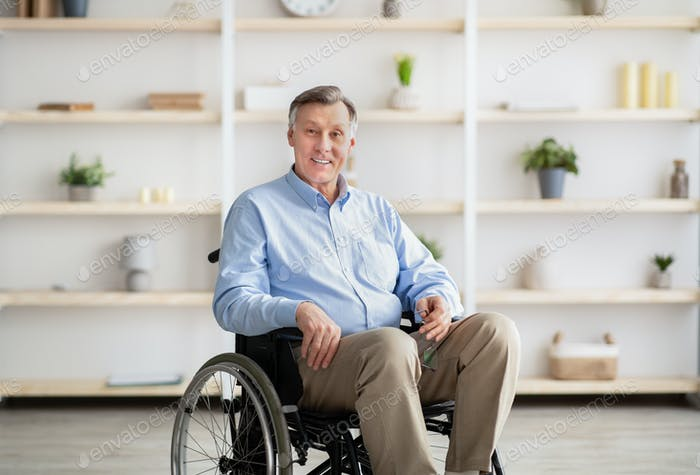 Joyful handicapped senior man in wheelchair smiling and looking at camera at retirement home