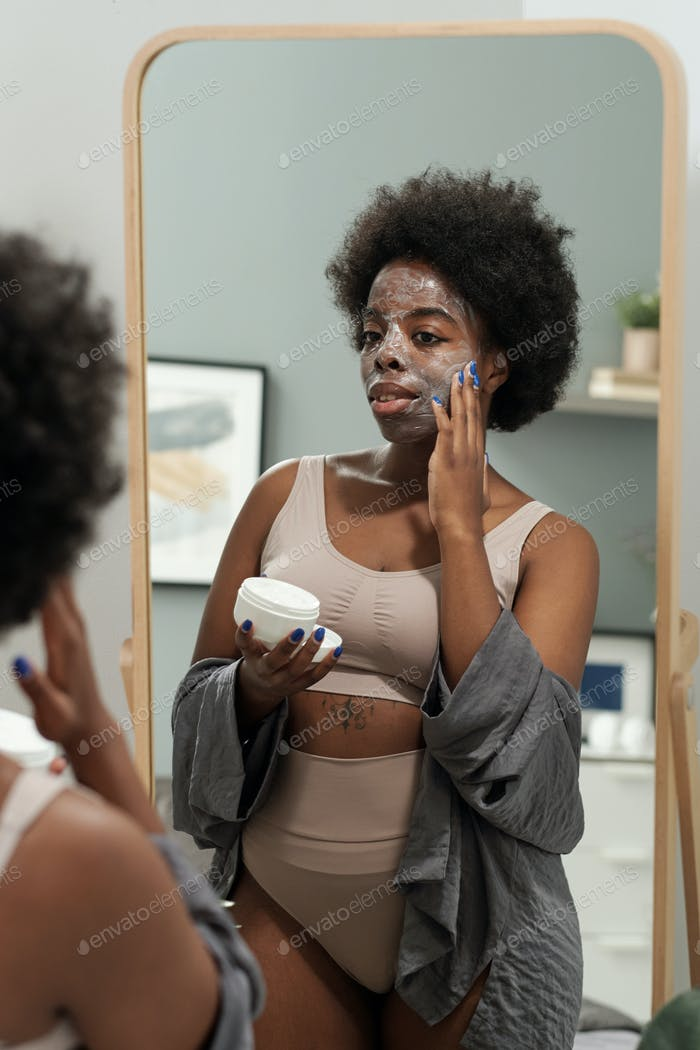 Young plus size woman in underwear taking care of her face