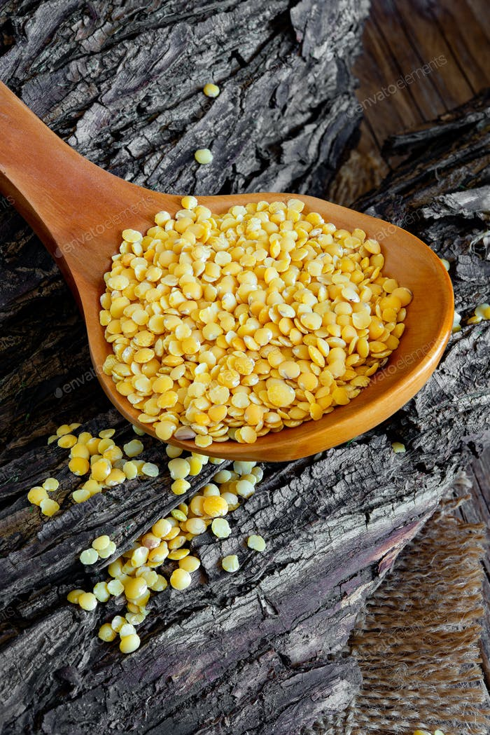 Wooden spoon with yellow lentils