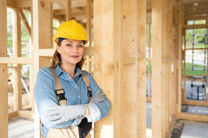 Proud female worker posing on building site with frame house construction in background