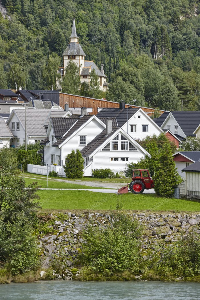 Norwegian traditional village, river and hill. Norway rural landscape. Vertical