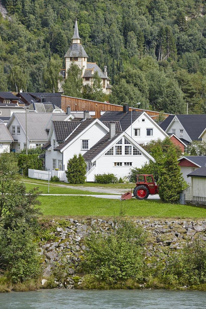 Norwegisches traditionelles Dorf, Fluss und Hügel. Norwegen ländliche Landschaft. Vertikal