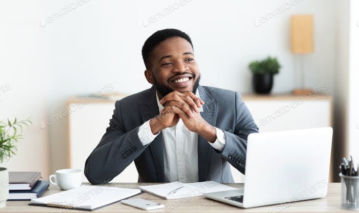 Pensive african businessman dreaming about something while working in office
