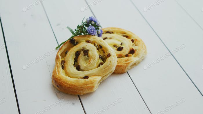 Delicious pastry with raisins on white wooden table