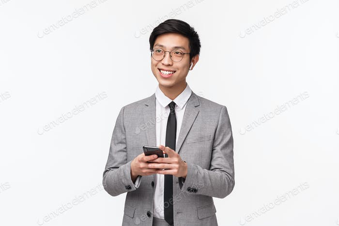 Waist-up portrait of stylish handsome asian businessmain in grey suit, listening music wireless