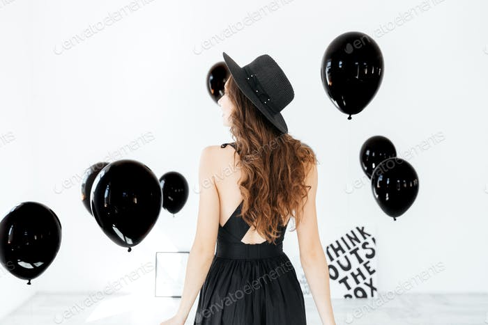 Back view of woman in black hat with air balloons