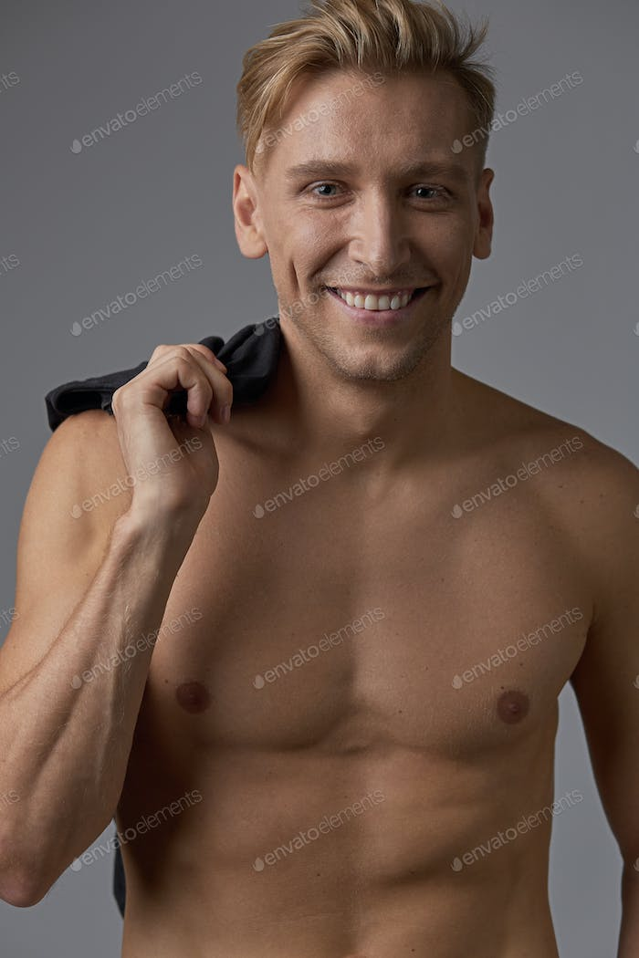 Handsome man with naked torso smiling