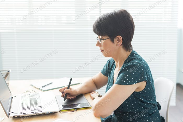 Business, web design and graphic art concept - middle-aged woman using pan sketch device