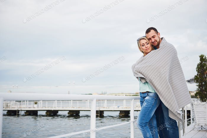 Happy young couple in a blanket, standing on the pier in the water