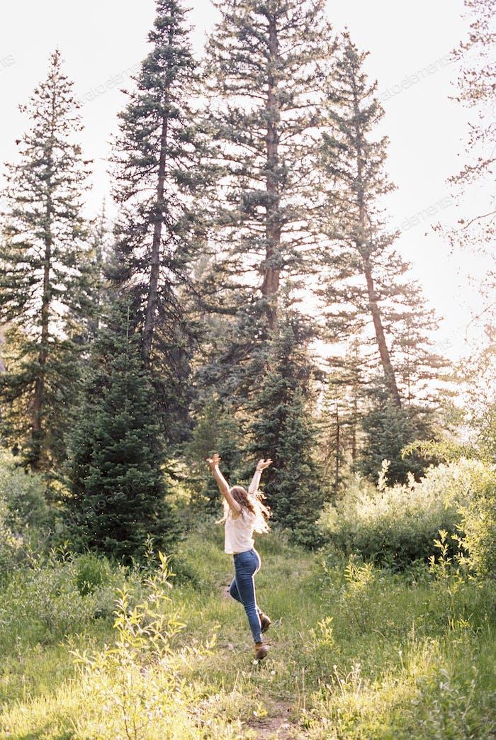 Frau springt vor Freude in einem sonnenbeleuchteten Wald.