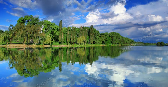 Panorama of cloudy sky reflection in the lake