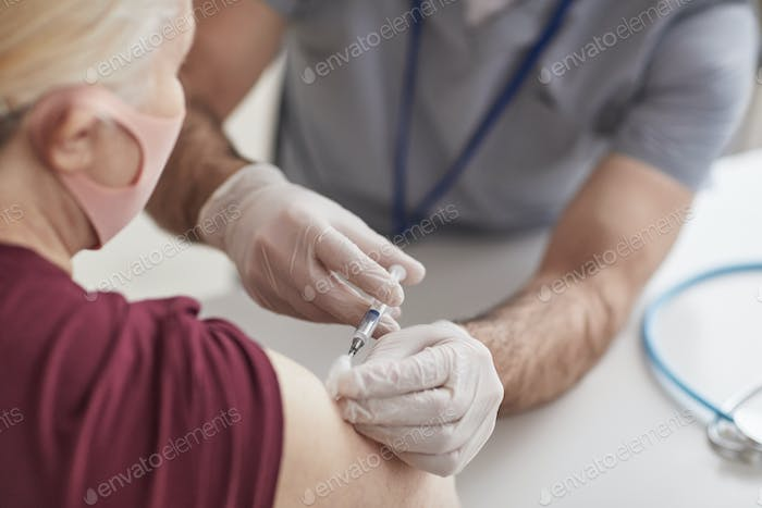 Doctor Vaccinating Senior Woman Close Up