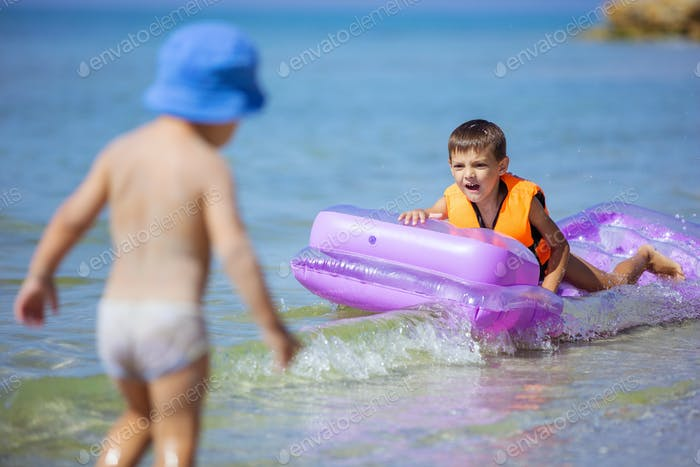 Young boys playing with floating air mattress