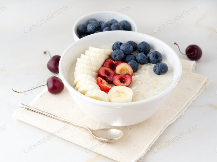 Large bowl of tasty and healthy oatmeal with fruits and berry for Breakfast, morning meal.