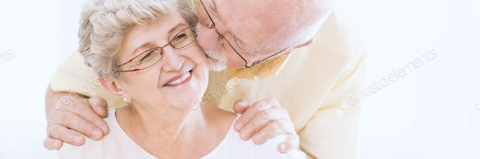 Elderly man kissing wife's cheek
