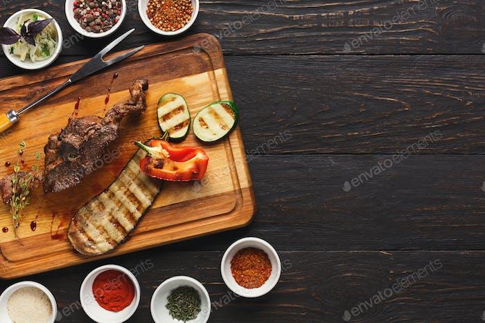 Gegrilltes Fleisch und Gemüse auf rustikalem Holzbrett