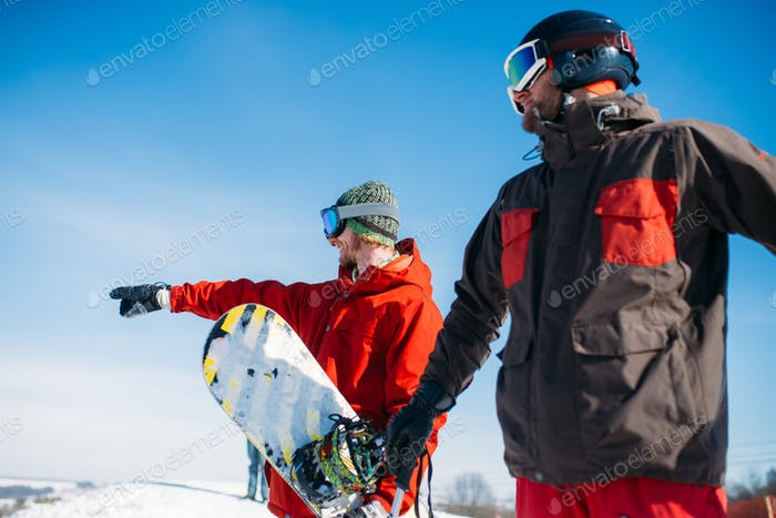 Snowboarder and skier poses on the top of mountain