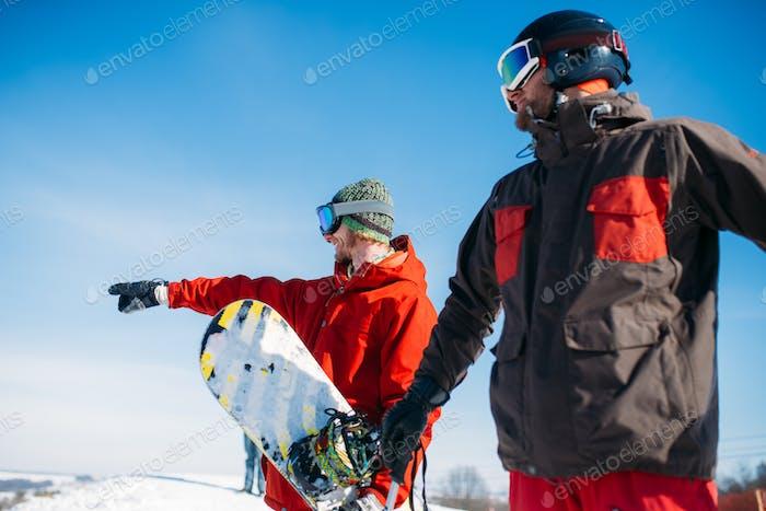 Snowboarder und Skifahrer Posen auf dem Gipfel des Berges