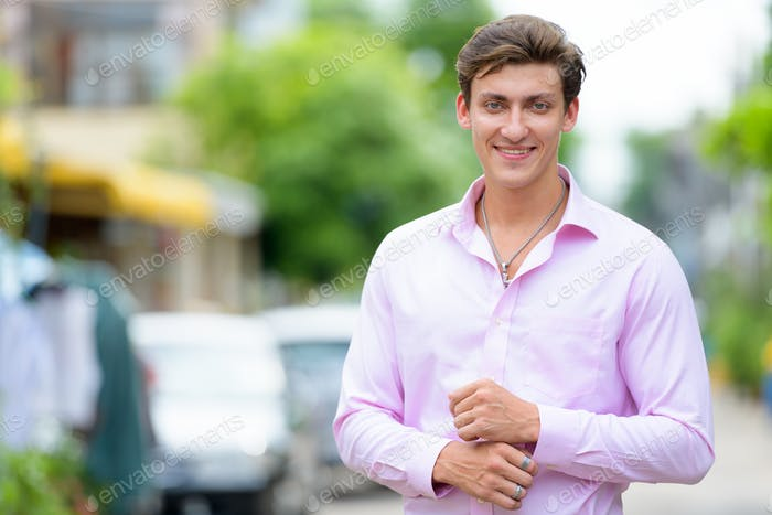 Portrait of happy young handsome businessman smiling outdoors
