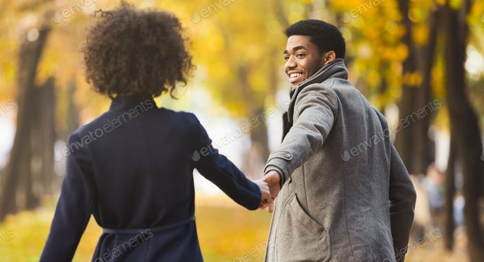 Follow me. Happy couple walking in autumn city park