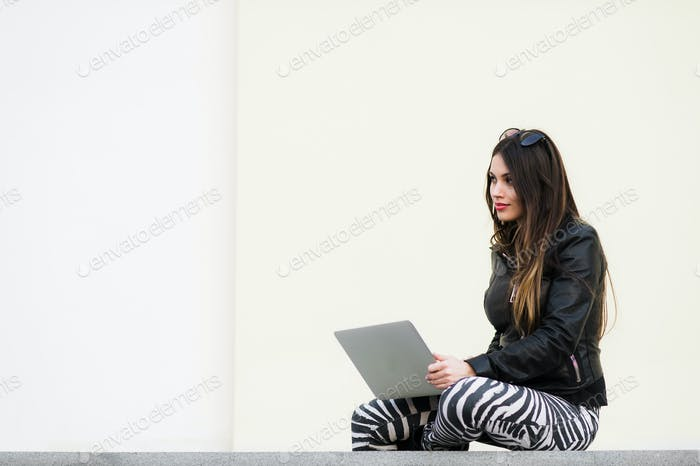 Pretty girl working with laptop sitting on concrete wall outdoors at the university campus