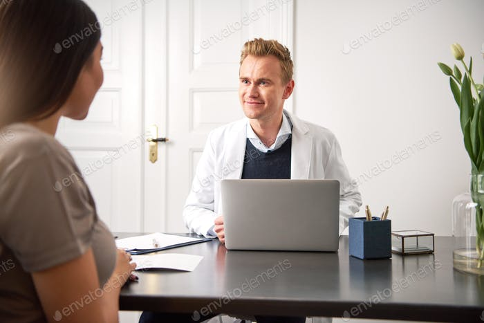 Cosmetologist consulting young woman sitting at laptop